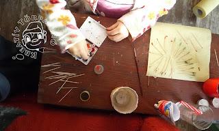 Szöveg: Előveszed/előveszi a fogpiszkálókat, majd egyesével belemártogatjátok/-tja a kiválasztott színbe/-kbe. Kép: Közelkép egy kicsi vörös asztalról, amin művészi össze-visszaságban leledzik fogpiszkáló, vízfesték, poharak, szívószál.