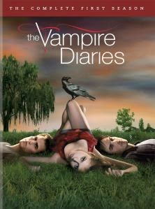 Cover art for S1 of The Vampire Diaries, featuring Stefan, Elena, and Damon lying on the grass together, being all provocative.