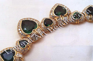 A yellow gold necklace, made up of heart-shaped emeralds set amid brilliant and baguette-cut diamonds.