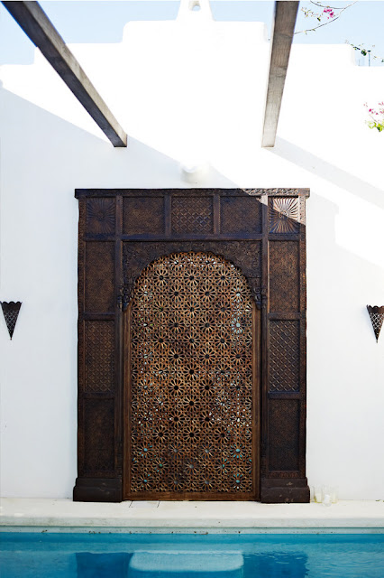 home with white washed walls, carved door and a pool