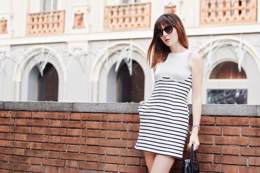 Irene Buffa wearing a Chic cocktail look featuring a striped raffia dress , white sandals and black accessories.