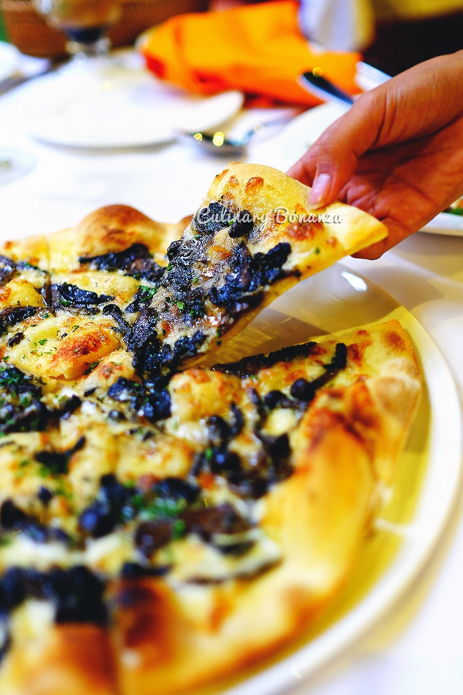 Pizza Con Funghi - Italian-style, crispy crusted pizza, topped with a medley wild mushroom, taleggio, fontina, thyme, truffle oil and shaved grana padano