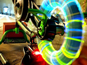 long exposure shot of glow sticks on bike wheel as it spins with varied speed