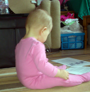 baby in pink onesie sits reading pieces of paper