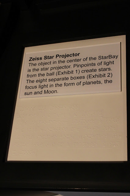 "In large print and Braille reads the following exhibit signage: ""The Zeiss Star Projector.  The object in the center of the StarBay is the star projector.  Pinpoints of light from the ball (Exhibit1) create stars.  The eight separate boxes (Exhibit 2) focus light in the form of planets, the sun and Moon."""