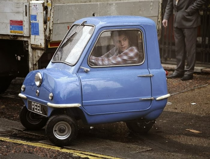 "The Peel P50 is a three-wheeled microcar originally manufactured from 1962 to 1965 by the Peel Engineering Company on the Isle of Man. Designed as a city car, it was advertised as capable of seating ""one adult and a shopping bag."" The vehicle's only door was on its left side, and equipment included a single windscreen wiper and only one headlight."