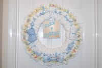 A diaper wreath with a few blue baby items and a plaque in the middle with the name John Porter decorated with It's a boy ribbon