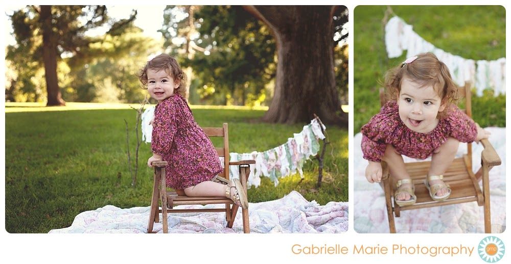 Playful 18 month old girl climbs into wooden folding chair.