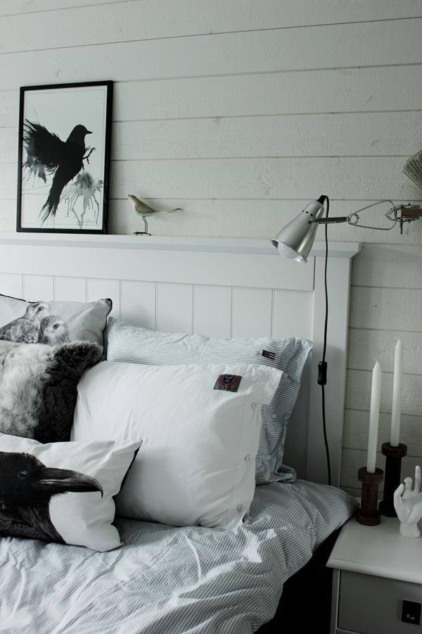 svartvit tavla med fågel, handmålad print, artprint fågel, fåglar i inredningen, inredning sovrum, vit hand som dekoration, kuddar med fågeltryck, vit panel på väggen, liggande panel, sänglampa