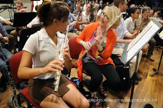 Una estudiante (I) de la Orquesta Juvenil del Conservatorio Amadeo Roldan intercambia con una integrante (C) de la Orquesta Sinfónica de Minnesota,  durante el ensayo realizado en el Teatro Nacional de Cuba, en La Habana, el 15 de mayo de 2015