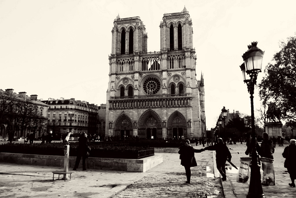 Couple holding hands in front of Notre Dame