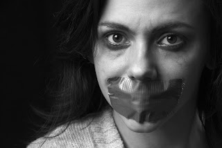 Image illustrating human trafficking, with woman with tape over her mouth.
