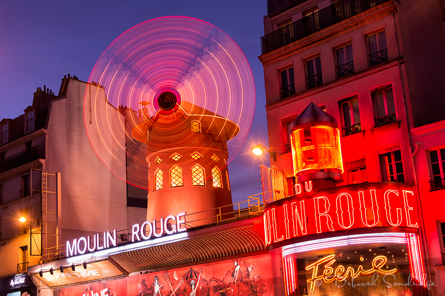 Monmarte area of Paris, Moulin Rouge at night with spinning windmill.