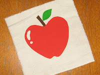 A square of calico with a 3-coloured print of an apple with stalk and leaf.
