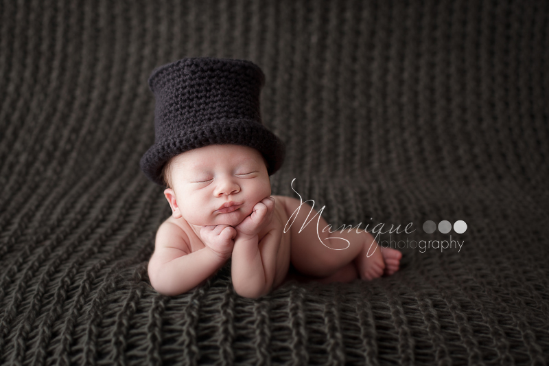 Newborn boy wearing Top Hat resting chin on hands
