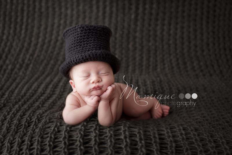 Newborn boy wearing Top Hat resting chin on hands