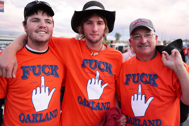 "Three guys with t-shirts that say, ""Fuck Oakland"" tailgating at Mile High Stadium in Denver before the Broncos vs. Raiders."