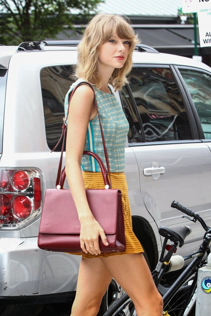 Taylor Swift parades long legs in a yellow mini skirt in New York City
