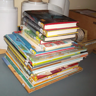 Stack of children's hardcover picture books and chapter-book fiction with white library tags on their spines. The stack is on a counter in front of rolls of dust-jacket protective covering.