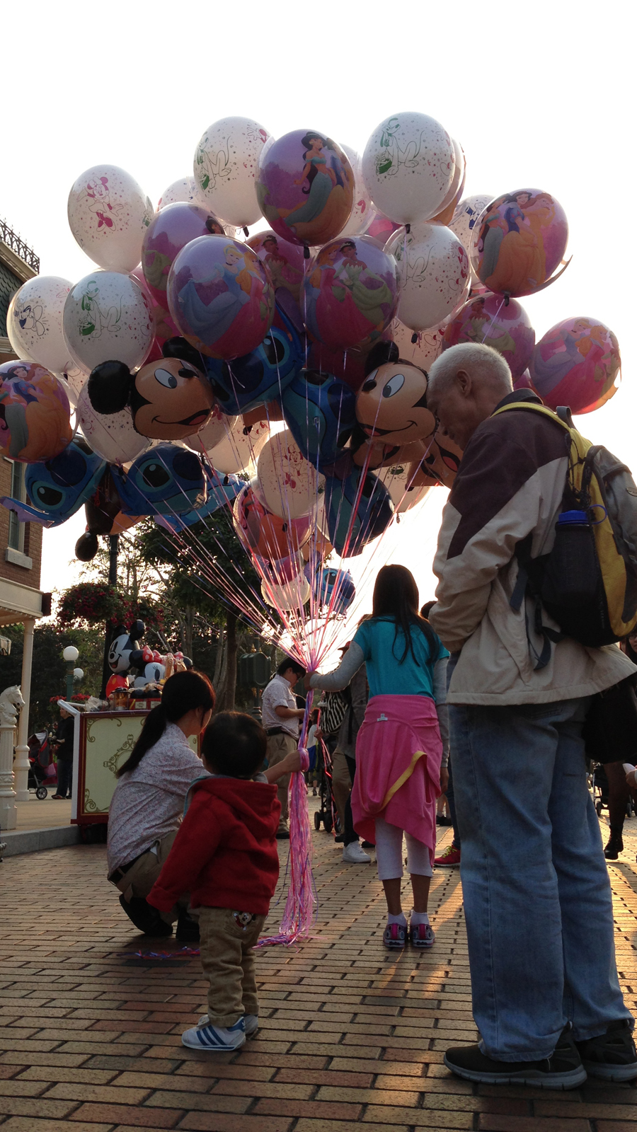 A toddler has fun with balloons at Hong Kong Disneyland. His grandfather would later look at me as I took a second photograph of the kid.