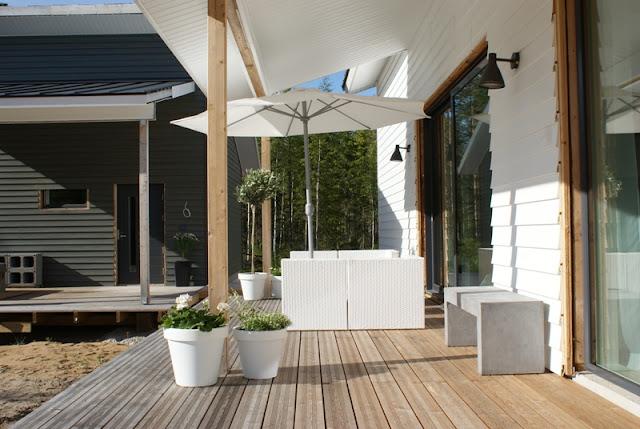 terassi, lehtikuusi, valkoinen ruukku, valkoiset kesäkukat, betonipenkki, valkoinen sohvaryhmä ulos, oliivipuu, lehtikuusi, saunatupa
