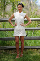 Olivia Munn strikes a pose in a short white dress by the wooden fense
