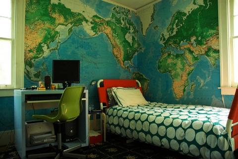 [A boy's room with a map wallpaper]