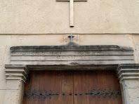 Detall de la llinda del portal de la capella decorada amb inscripcions i motllures