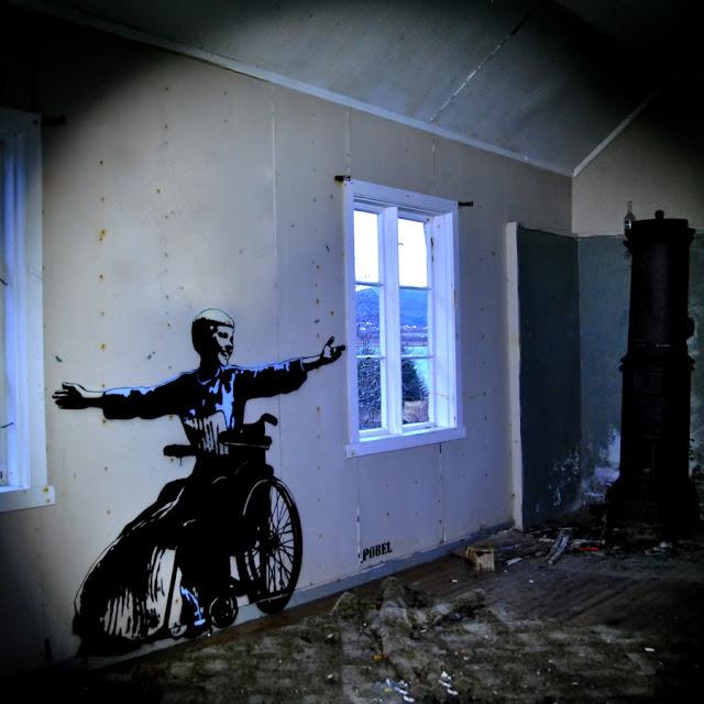 Graffiti-vægmaleri af pige i kørestol, der byder velkommen i forfaldent hus