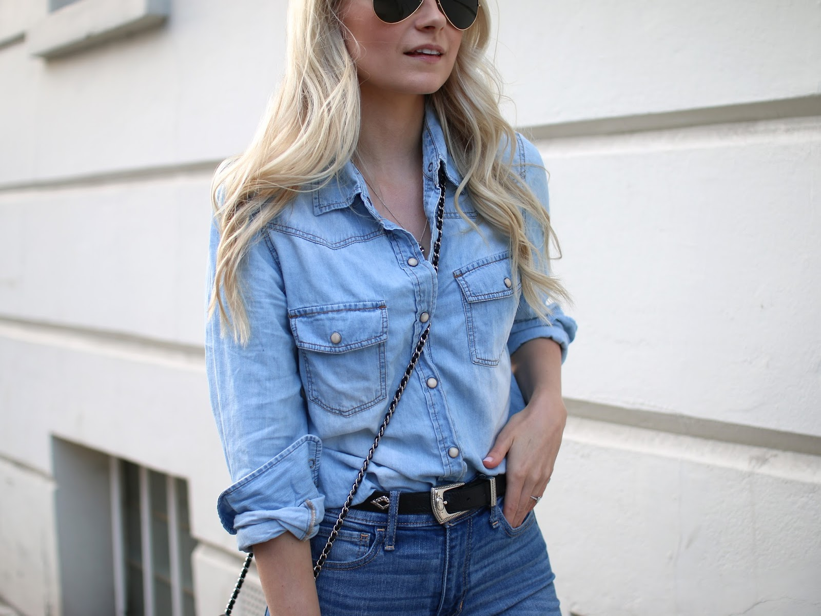 a blonde women poses for picture at sunset in an all blue outfit and vintage western belt and chanel purse