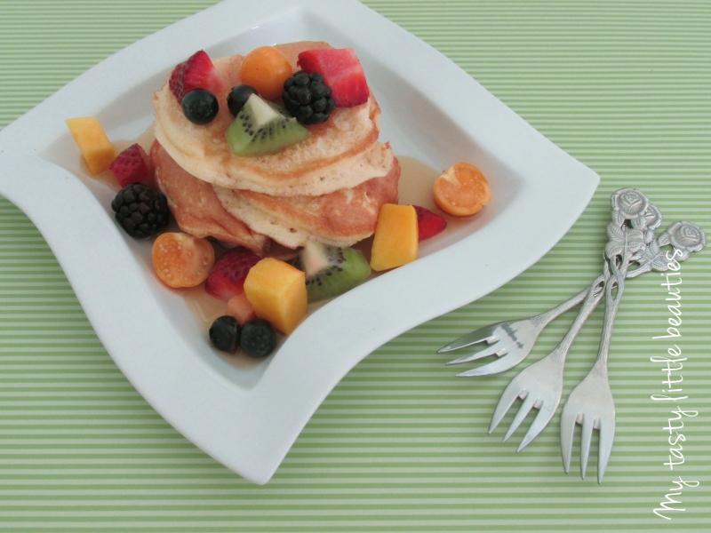 Pancakes mit Obst auf einem Teller mit drei Gabeln