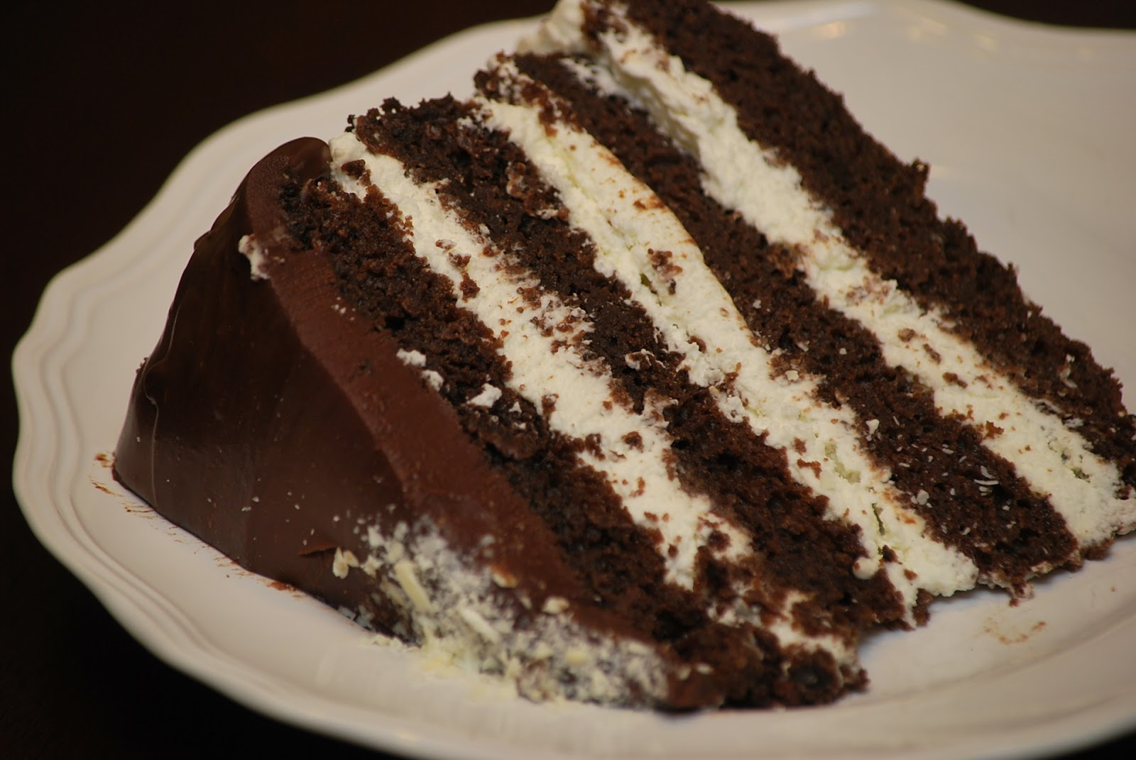dark chocolate four layer cake filled with fluffy whipped cream and ...
