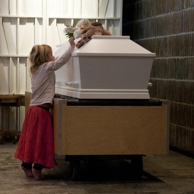 Tre-årig lille pige vil op og sidde hos sin mor, på hendes kiste - fra udstilligen Memento Mori, ved Trille Skjelborg