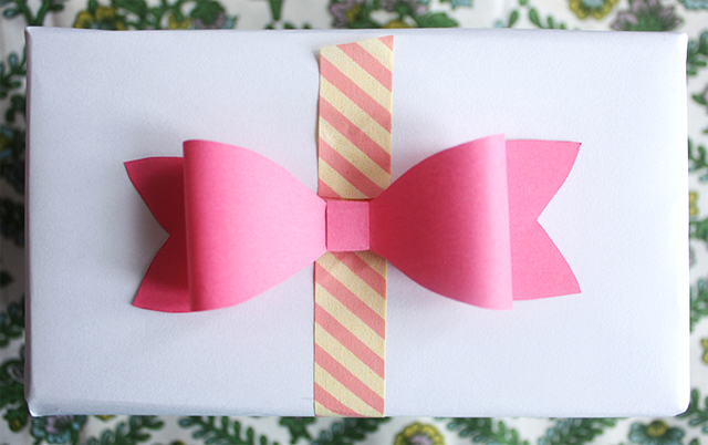 cute paper bow on present with wrapping