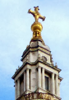 A golden ball and cross on top of an elaborate tower