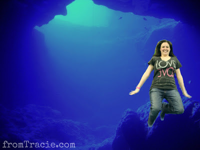 Tracie floating by a rock underwater