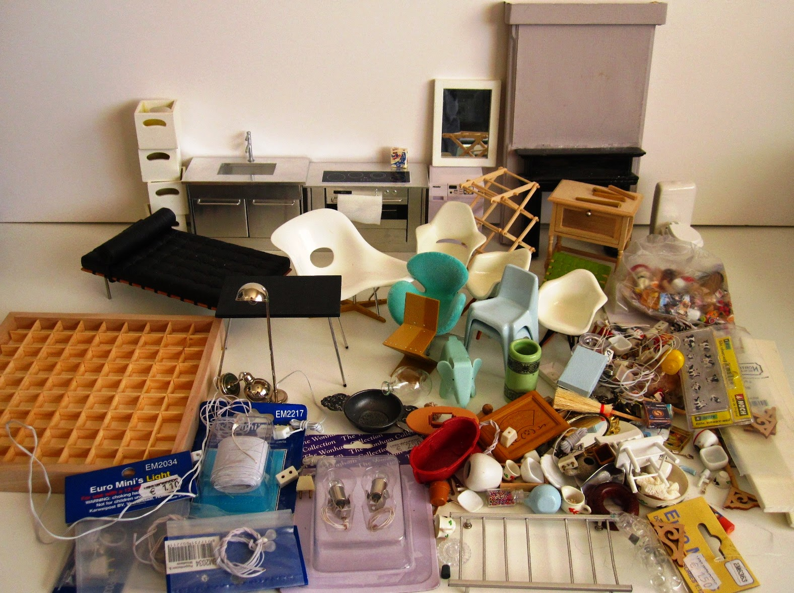 A large selection of modern miniature furniture and accessories, laid out on a  white workbench.