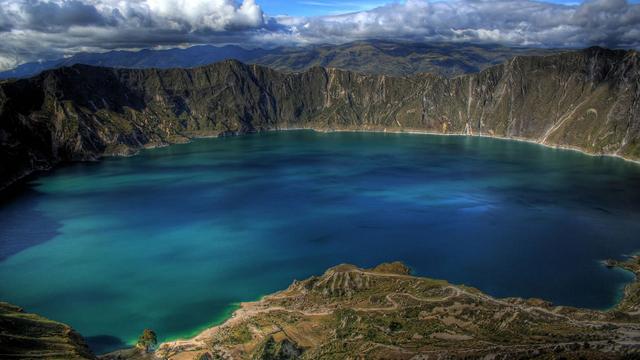 lago de forma irregular cercado de rochas e água de cor verde