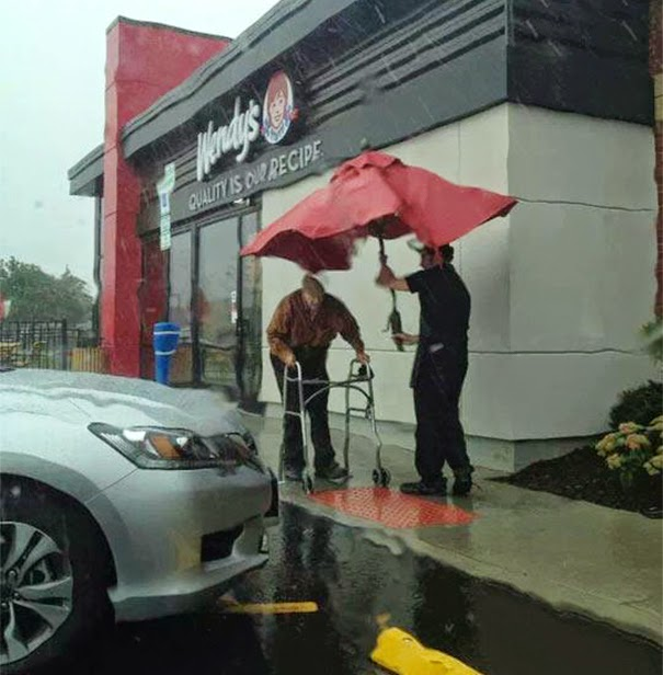 20+ Photos That Will Restore Your Faith In Humanity - Wendy's Employee Removes Umbrella From Table To Protect Elderly Man From Rain