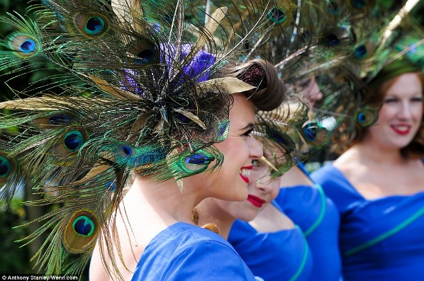 The Tootsie Rollers in elaborate peacock feather headgear and fitted cobalt blue dresses on Ladies' Day of Royal Ascot 2014