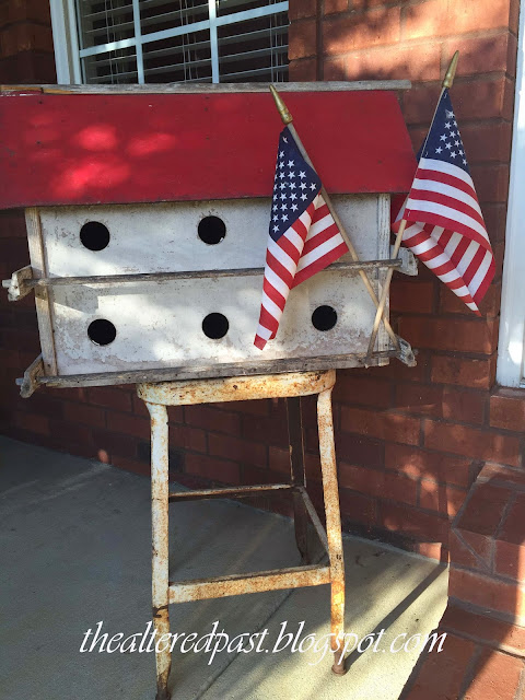 vintage birdhouse with red roof and American flags