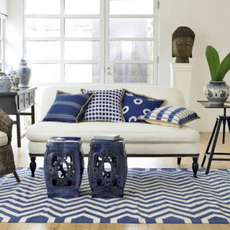 Asian inspired worldly coastal space with blue and white pillows