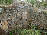 Fotografia d'una de les estances del recinte jussà, del Castell de Sant Jaume, amb un portal tapat