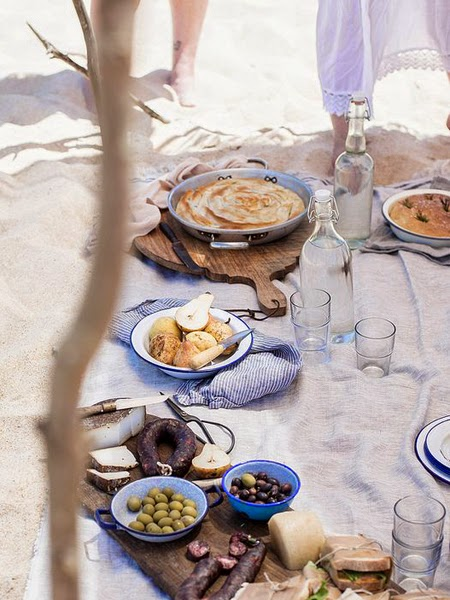 Duże talerze z jedzeniem na kocu, który leży na piasku nad morzem