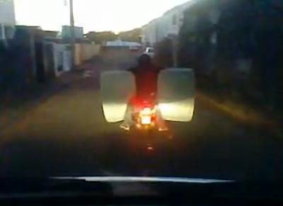 Homem conduz mota e transporta colchão ao mesmo tempo
