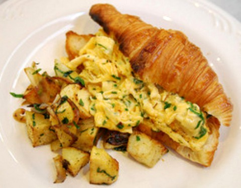 Herb flavored scrambled eggs and fried potatoes