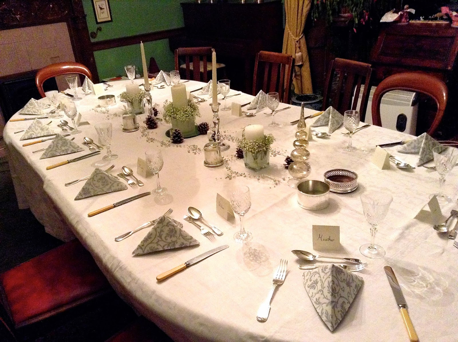 Christmas dinner table with white & silver napkins, candles, ornaments & pine cones
