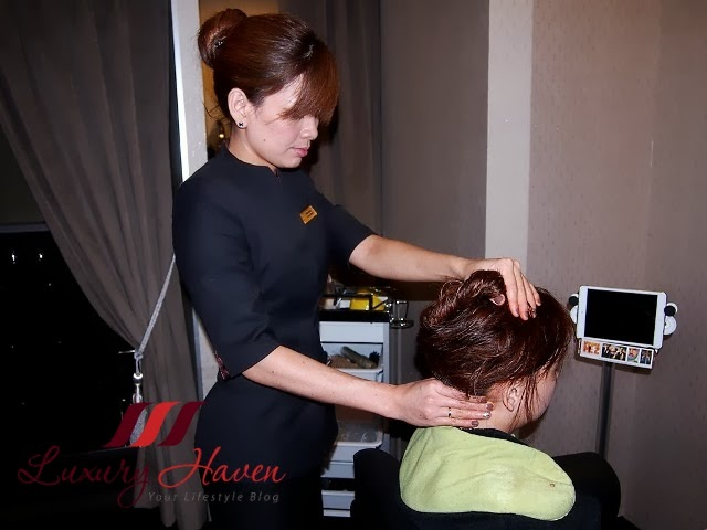 therapist giving origin luxe scalp treatment head massage