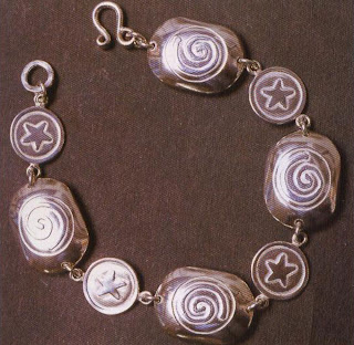 This bracelet was made by a series of domed pieces, soldered together, with simple stamped pieces between them