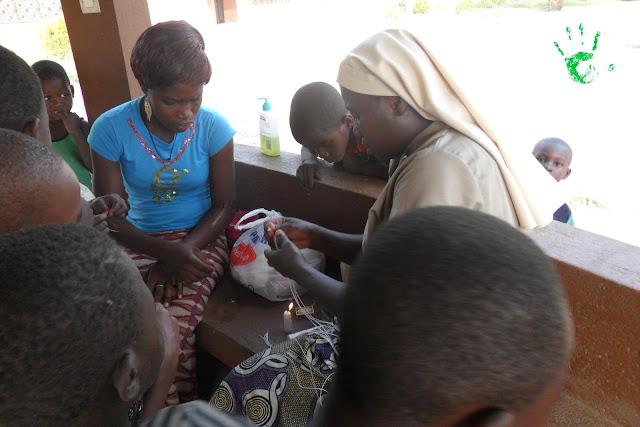 Suor Colette e la maestra della scuola materna danno i fili ai bambini